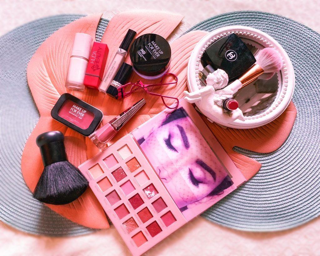 foto dall'altro in cui si vedono cosmetici: correttori rossetti pennelli palette ombretti. il potere del make-up è grande