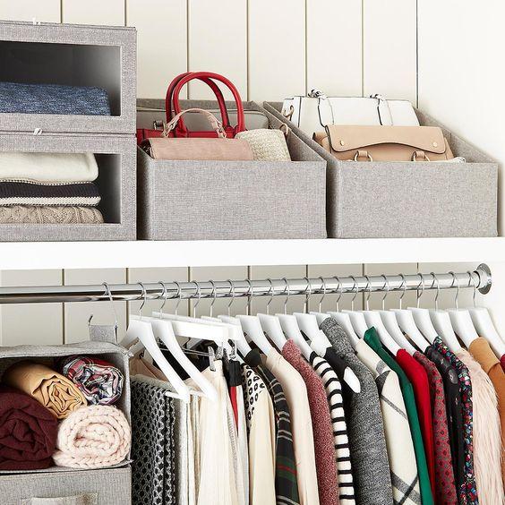armadio ordinato con diversi spazio per gli abiti piegati. il decluttering rende visisbile anche il cambio immagine