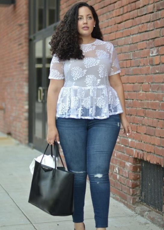 donna indossa jeans stressi e una blusa bianca. ha forme morbide e lunghi capelli mossi. tiene in mano una borsa nera. ecco come vestirti bene
