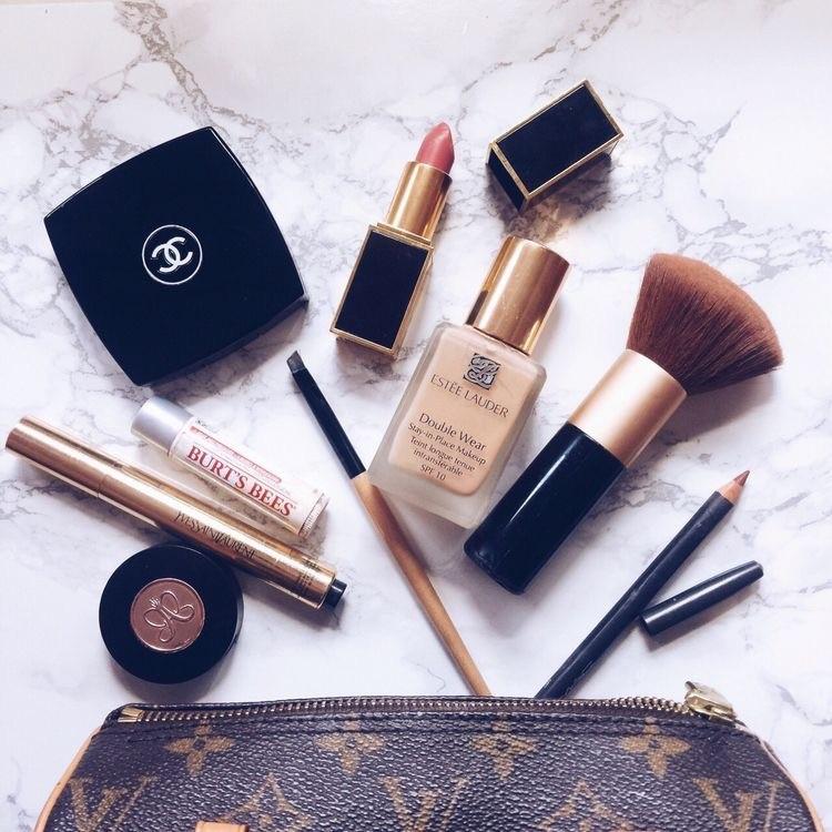 Alcuni cosmetici per il make-up di base, sparsi su un tavolo. Ombretto, matita, blush,mascara, fondotinta sopra una pochete Vuitton