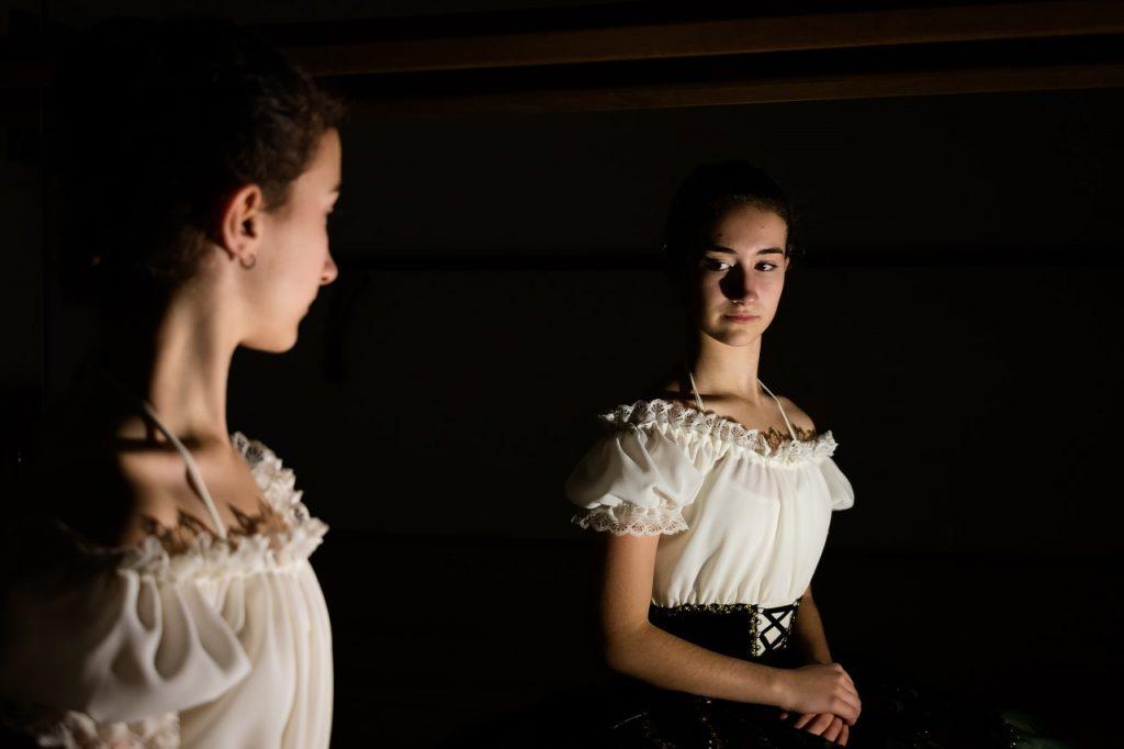 donna si guarda allo specchio dubbiosa. il suo corpo non le piace. si vergogna