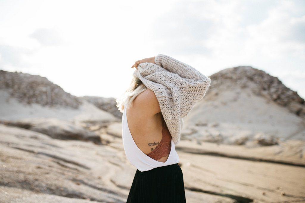 donna si spoglia su una spiaggia. Toglie il maglione e copre il viso. La vergogna nel mostrarsi in spiaggia è molto comune.