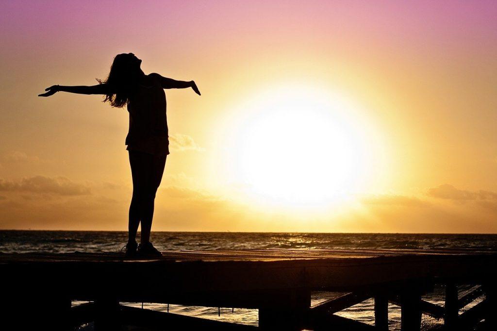 donna in controluce al tramonto. apre le braccia in segno di libertà. vergognarsi del proprio corpo non deve essere un limite
