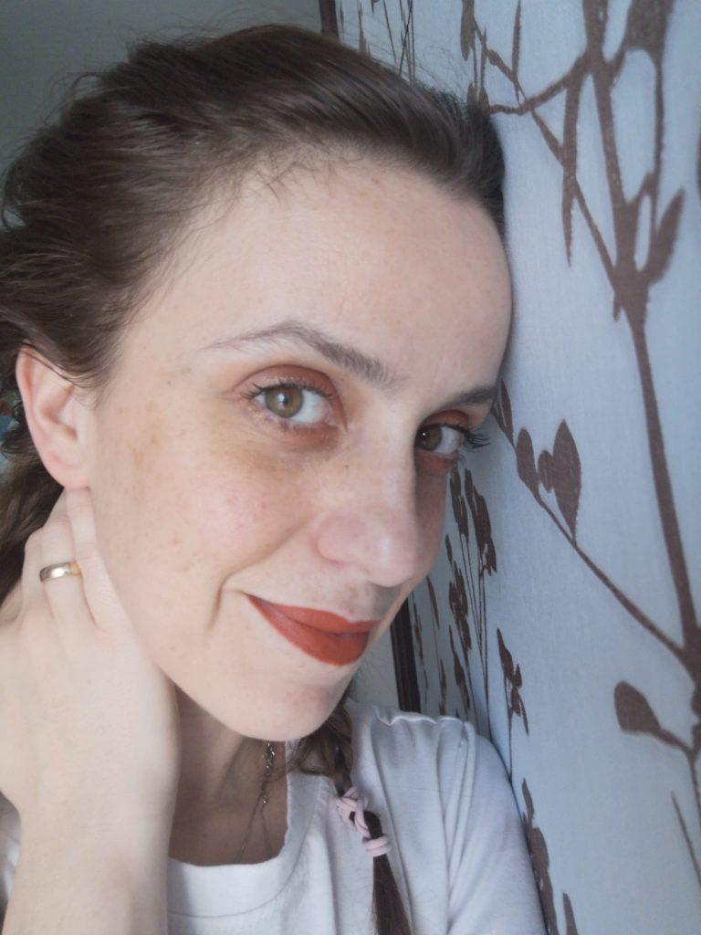ritratto di donna volto a tre quarti poggiato ad una parete azzurra. indossa rossetto corallo e ha lunghe trecce.
