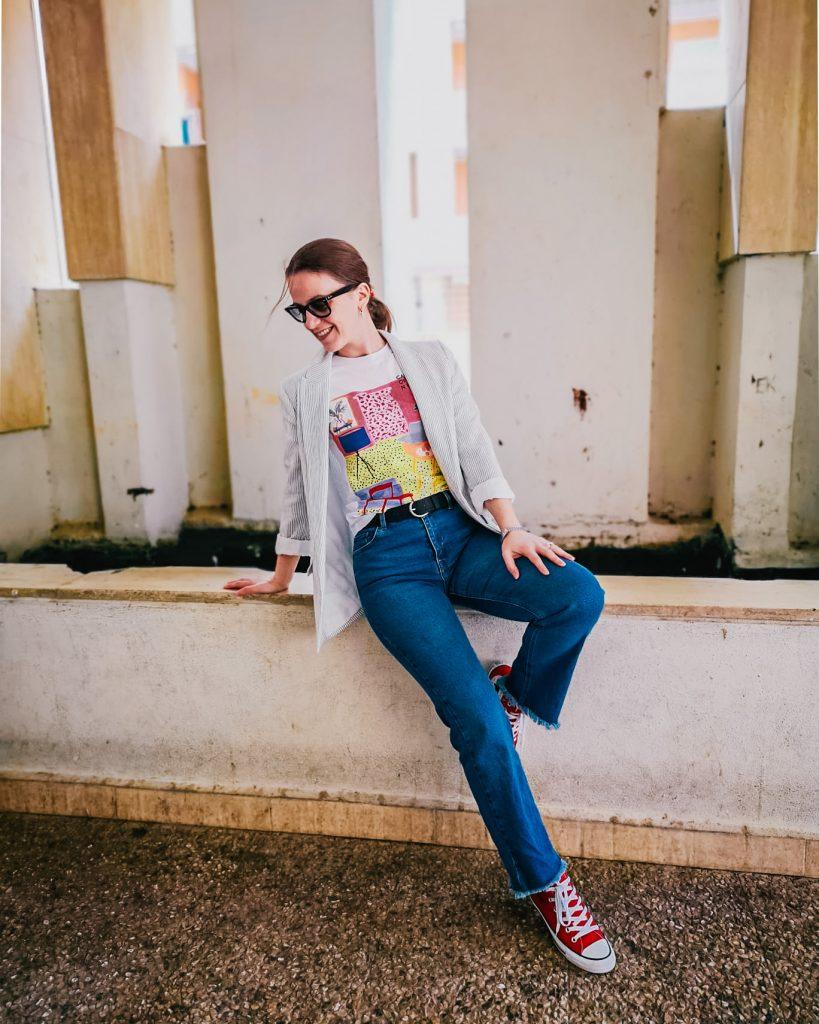 i jeans autunno 2020. donna in foto seduta su un muretto indossa jeans flared converse rosse e blazer a righe bianche