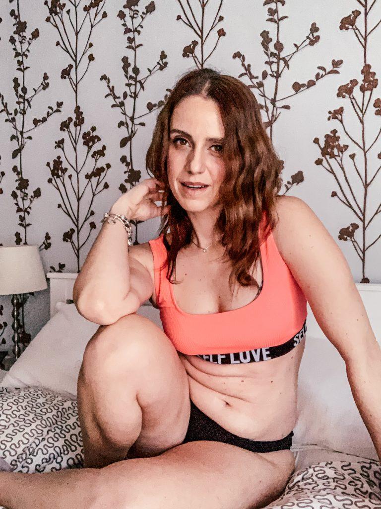 donna seduta sul letto. ha una gamba piegata su cui poggia il gomito. si vedono le pieghe della pancia. sorride felice del suo corpo