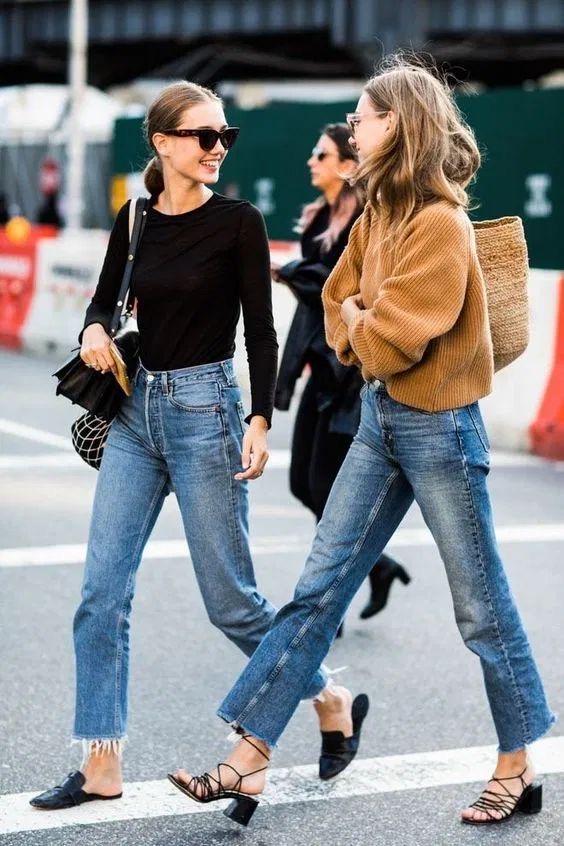 due donne passeggiano per strada indossano jeans flred scarpe con tacco. una ha una maglia aderente nera l'altra una maglia over arancione