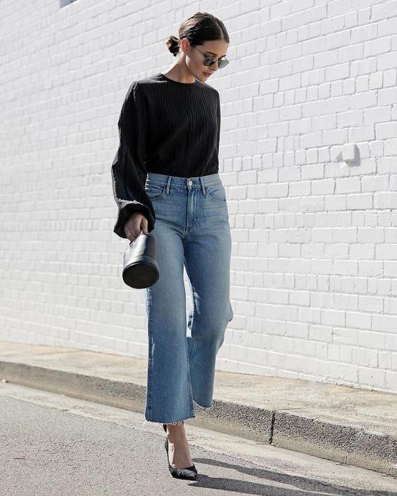 donna in jeans flared corto alla caviglia. indossa maglia dentro ai jeans una mini borsetta nera e capelli raccolti