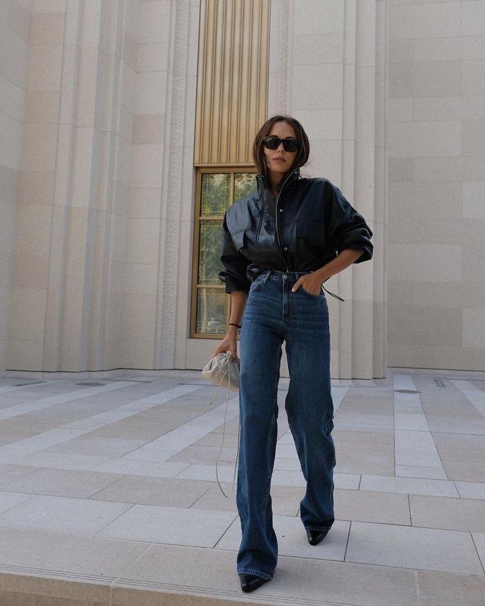 foto di donna indossa jeans wide leg a gamba larga con un giubbotto in pelle e stivali neri con tacco. un must jeans autunno 2020