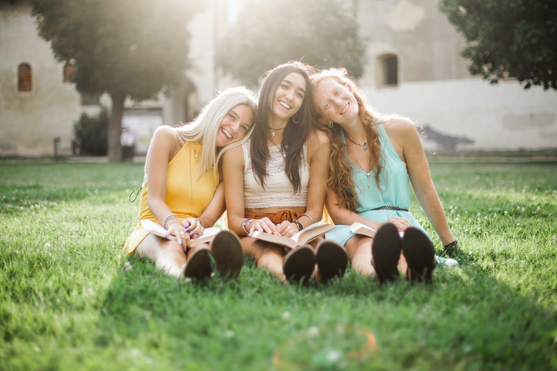 tre amiche sono sedute su un prato con la testa poggiata l'una sulla spalla della l'altra.
