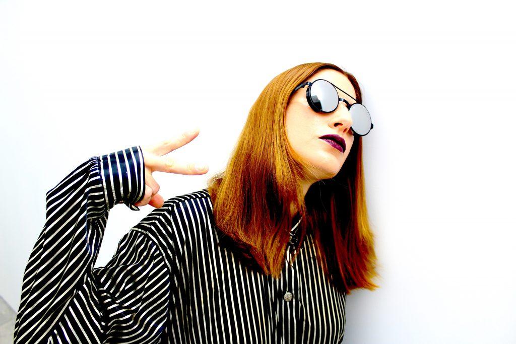 donna in posa a tre quarti. indossa occhiali tondi ha capelli rossi e una camicia a righe bianche e nere. con la mano fa il gesto della vittoria. la disobbedienza nella bellezza è libertà