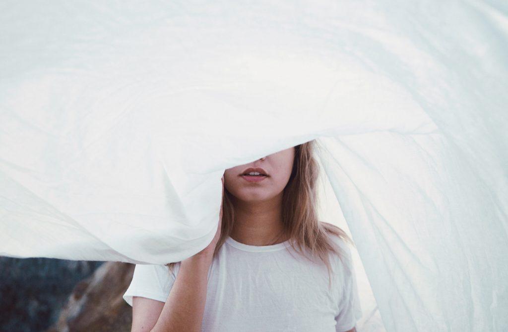 donna nascosta dietro lenzuolo bianco. si vedono solo labbra e naso. la chirurgia plastica sono effetto di oggettivazione e auto-oggettivazione