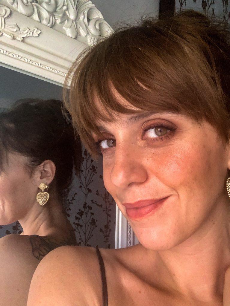 selfie di donna davanti allo specchio. Sorride, indossa orecchini a cuore e ha i capelli alzati. imparare a fregarsene da una grande soddisfazione