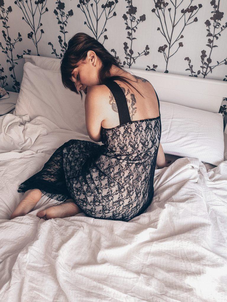 imparare ad accettare il proprio corpo. Donna seduta su un letto disfatto con biancheria bianca. Indossa abito in pizzo nero. Si accarezza i capelli, è scalza.